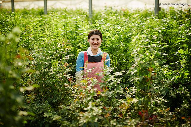 「温室のバラの中に立つ笑顔の農婦」(c)hi-bi/amanaimages