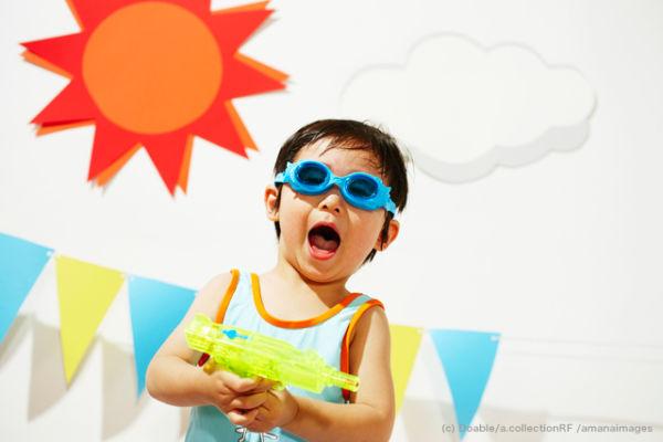 夏の日差しの中水鉄砲で遊ぶゴーグルの男の子