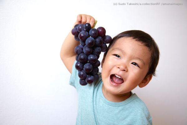 ぶどうを笑顔で持つ子供