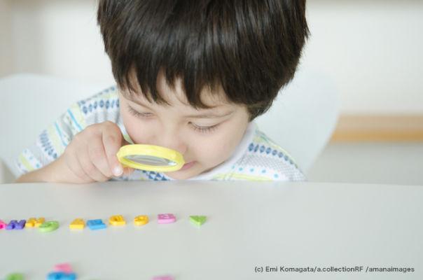 アルファベットを虫眼鏡で見ている子供