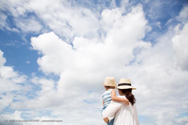 青空を背景に男の子を抱っこしている母親の後ろ