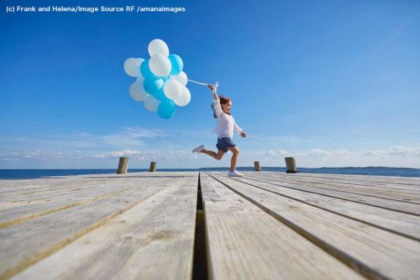 Young girl running on wooden pier, holding bunch of balloons