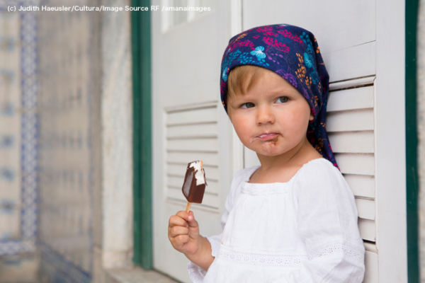 Portrait of female toddler leaning against shutters eating ice lolly, Beja, Portugal