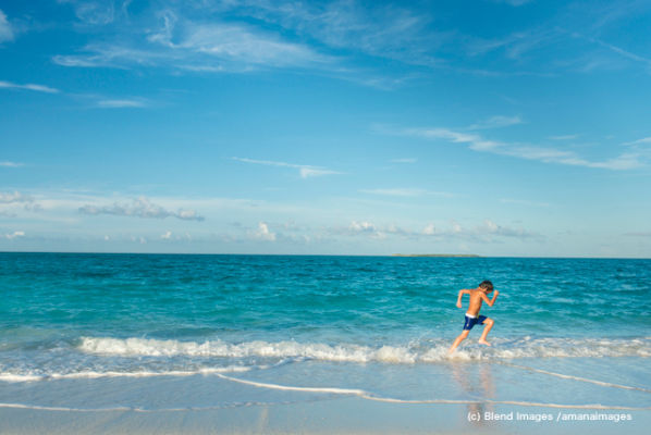 Hispanic boy running on beach