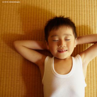 畳の上に寝転ぶ男の子