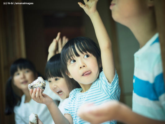 おにぎりを食べながら手を上げる子供たち