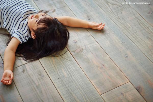 フローリングの床に寝転ぶ女の子