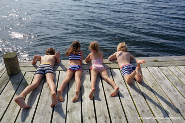 Boys and girls laying on dock looking down at lake