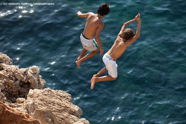 Two boy having fun while diving from rock into Mediterranean Sea, Nice, France