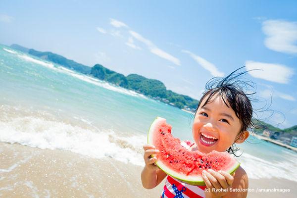 夏の海辺でスイカを食べる女の子
